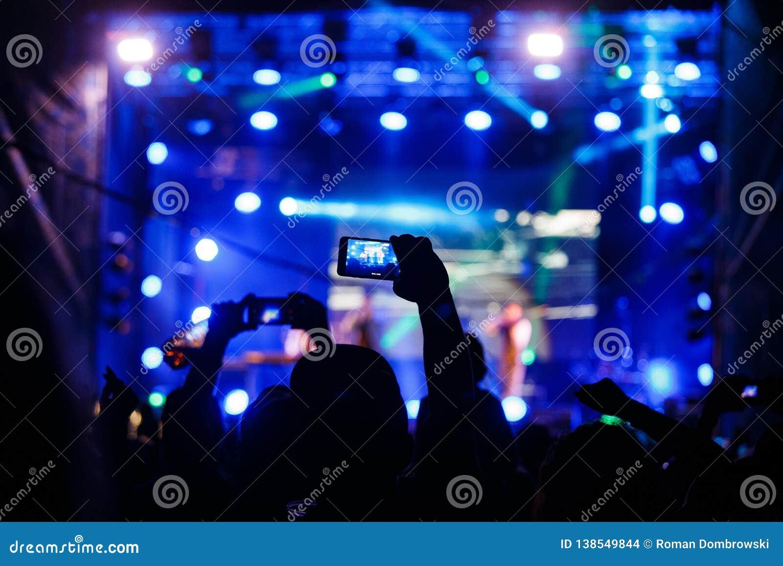 Ludzie przy koncertowym mknącym wideo lub fotografią