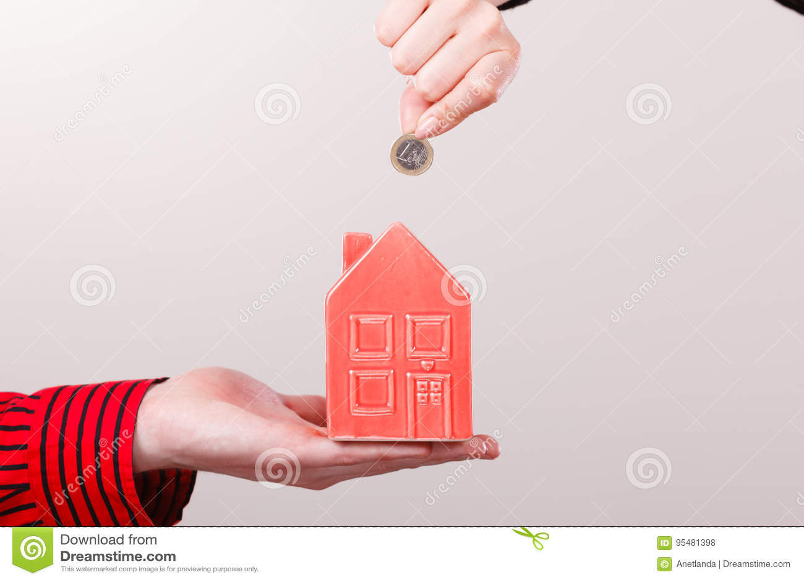 Ludzie ręk z małym domem i srebną monetą