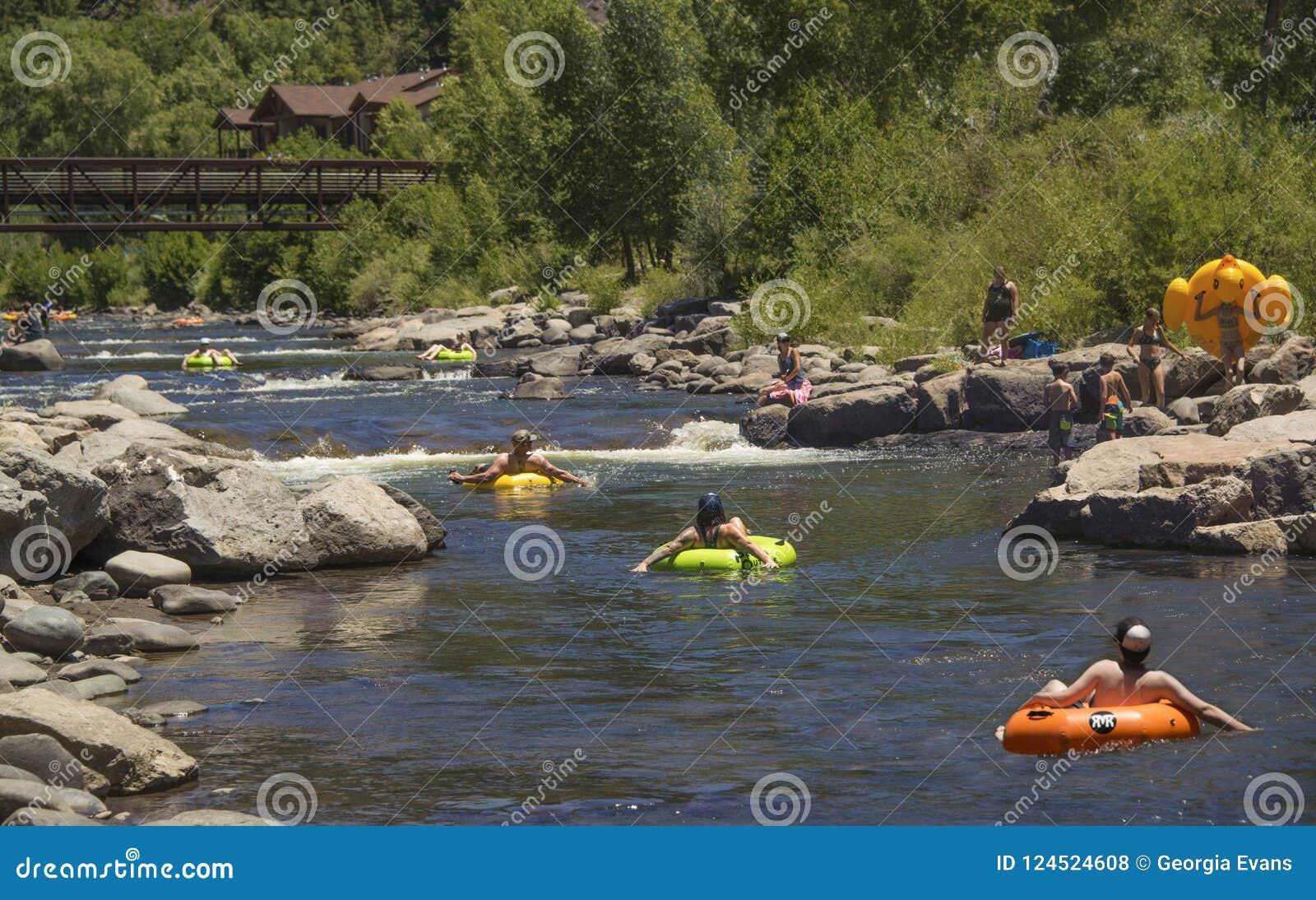 Ludzie rodzin ma zabawę chłodniczą z unosić się w nadmuchiwanych tubkach zestrzelają San Juan rzekę na gorącym letnim dniu w Pago