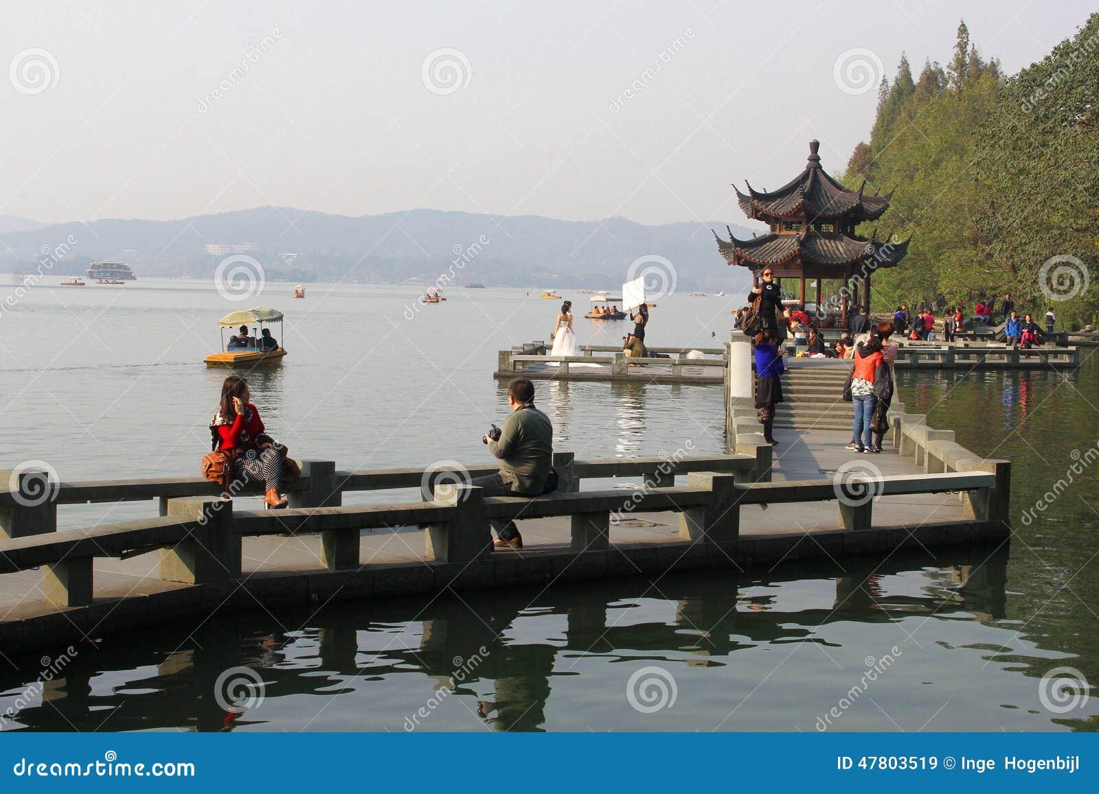 Ludzie są relaksujący wzdłuż Unesco Zachodniego jeziora w Hangzhou, Chiny