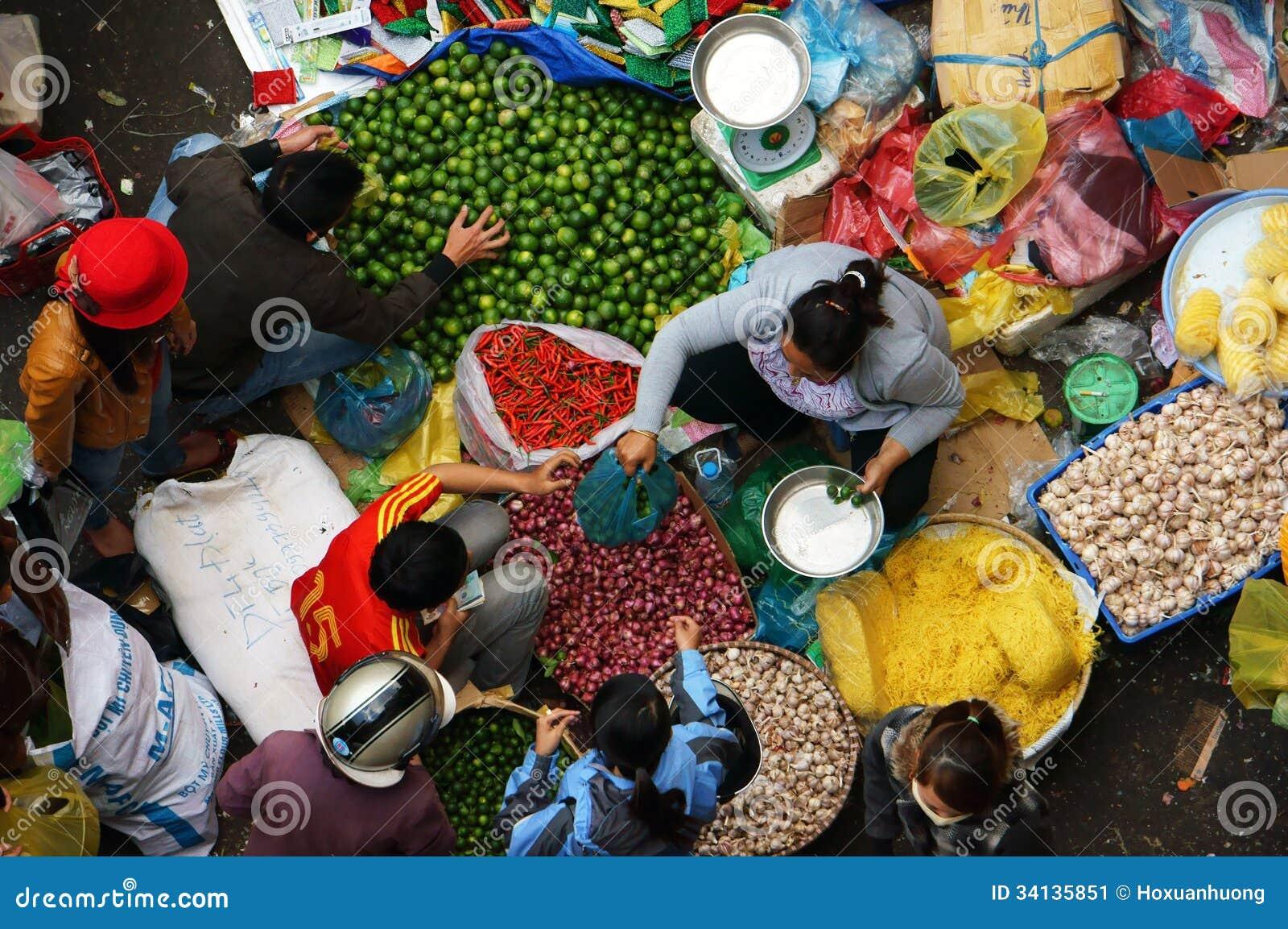 Ludzie sprzedają pikantność i kupują przy na wolnym powietrzu rynkiem. DA LAT, WIETNAM LUTY 8, 2013
