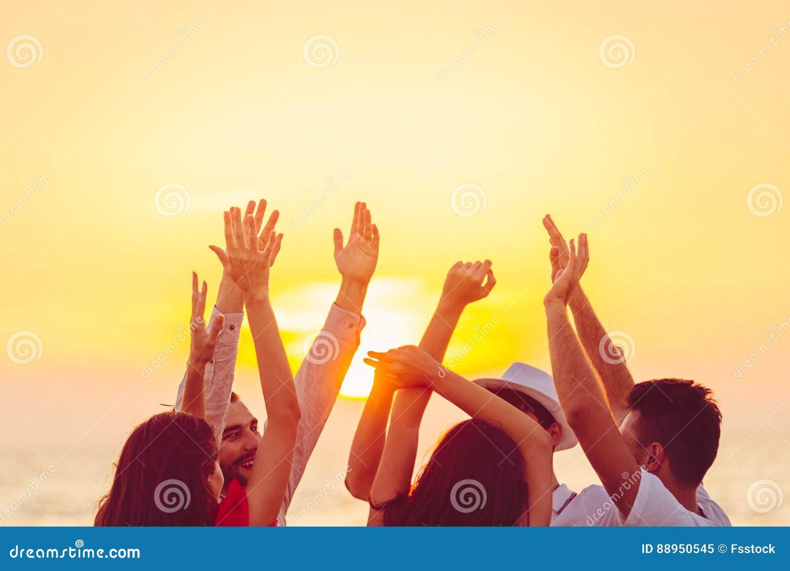 Ludzie tanczy przy plażą z rękami up pojęcie o przyjęciu, muzyce i ludziach,
