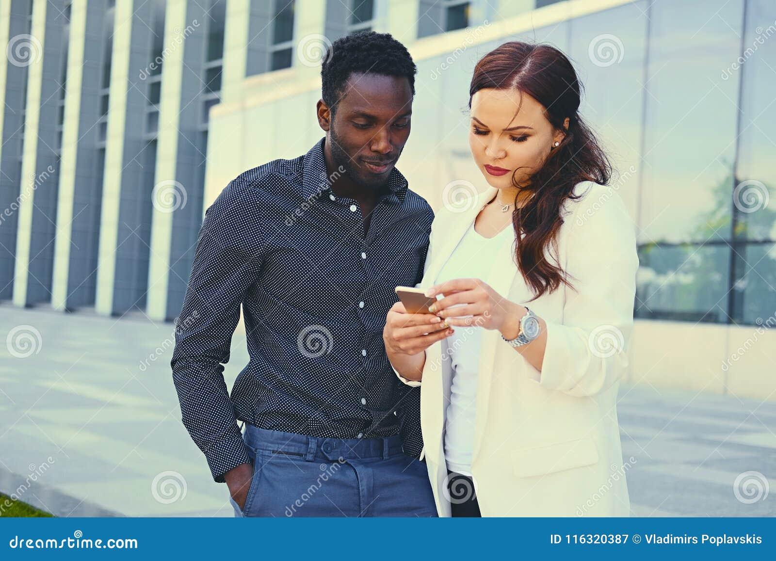 Ludzie używa smartphones nad nowożytnym budynkiem