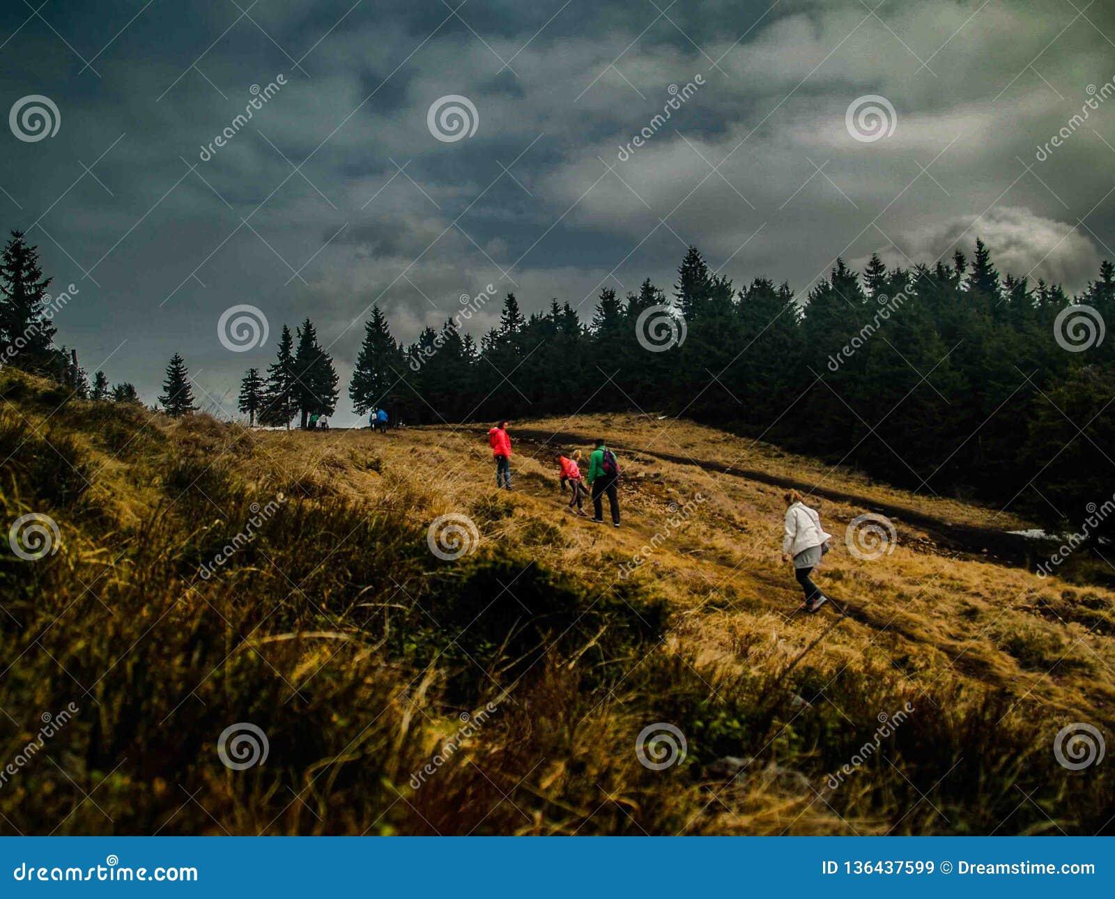 Ludzie wspina się na ich sposobie w chmurzącej pogodzie Madarasi Hargita Harghita Madaras podczas jesieni,
