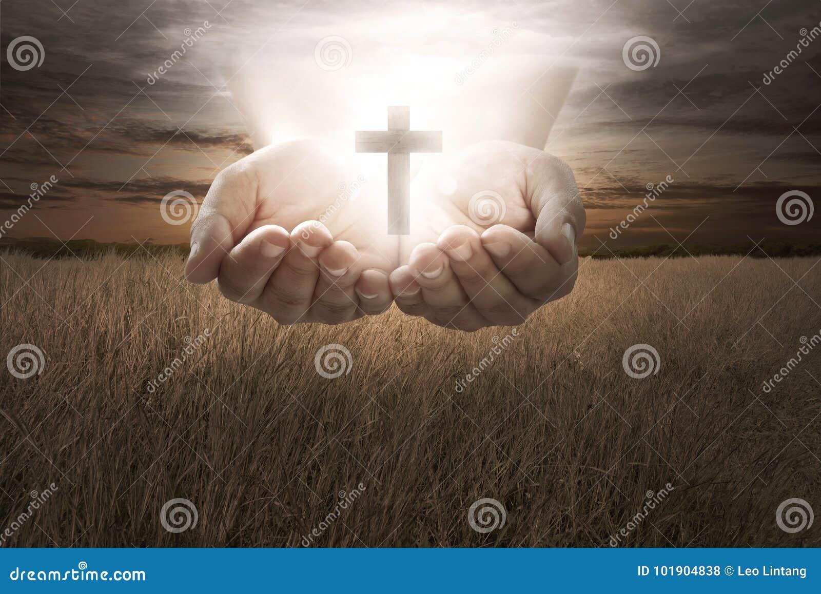 Ludzki ręka chwyta chrześcijanina krzyż
