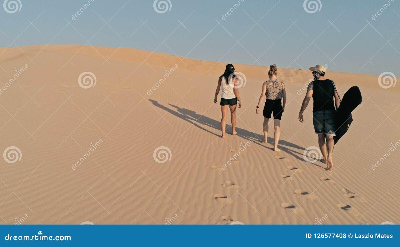 Luftbild von den jungen Leuten, die oben auf eine Sanddüne zur Spitze in einer schönen Wüstenumgebung gehen