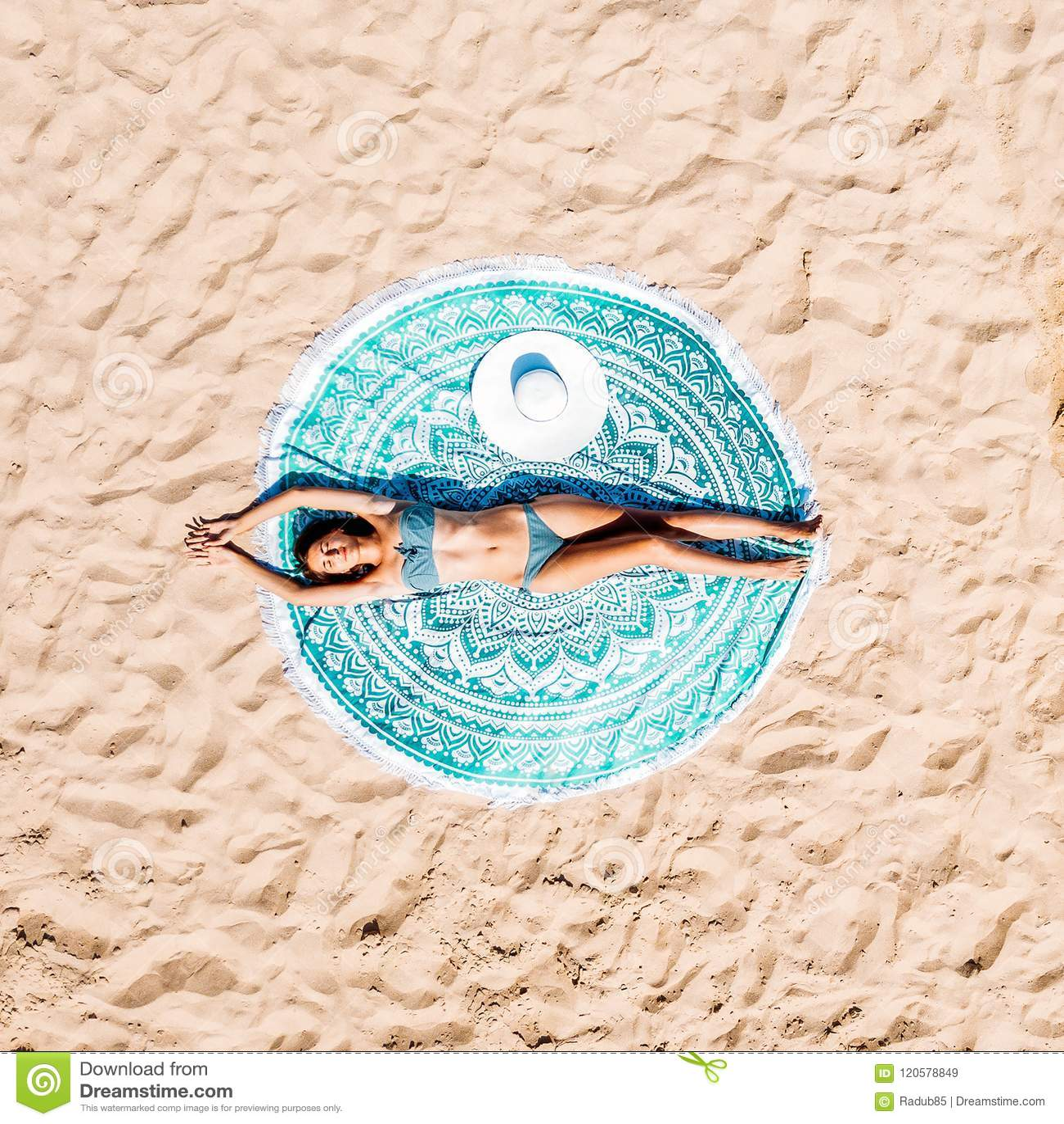 Luftbrummen-Ansicht der Frau im Badeanzug-Bikini, der auf rundem Türkis-Badetuch nahe dem Ozean sich entspannt und ein Sonnenbad