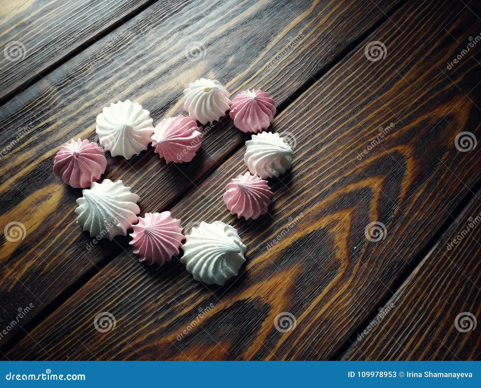 Luftig rosa färg- och vitmaräng på träbakgrund