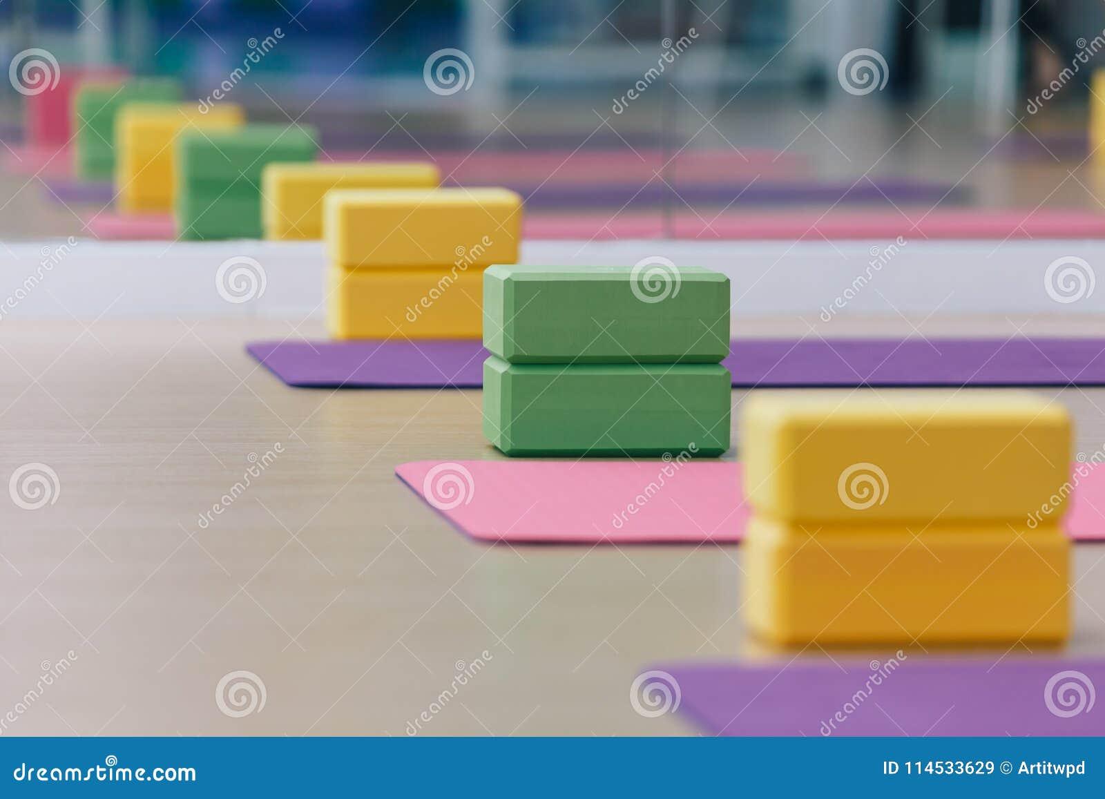 Lugar colorido dos blocos e das esteiras da ioga no assoalho de madeira da textura Apronte para a classe da ioga