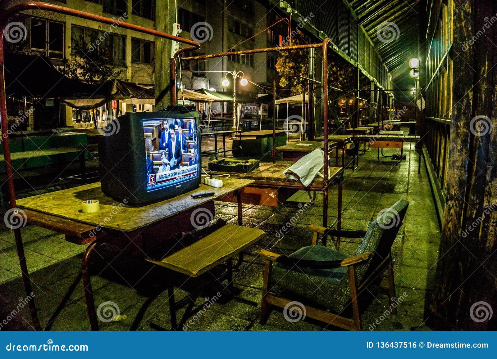 Lugar de descanso com uma televisão que pertence a um protetor de noite em Eger, Hungria que toma do salão do mercado da cidade n