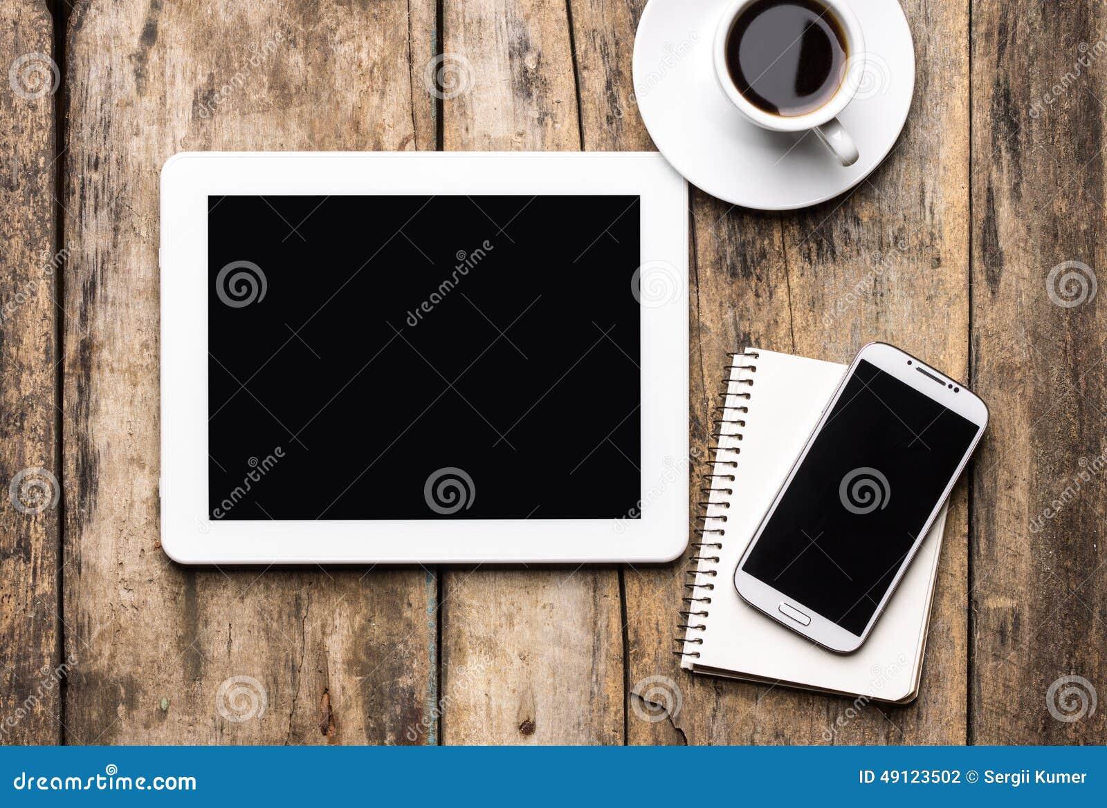 Lugar de trabajo móvil con la tableta, el teléfono y la taza de café