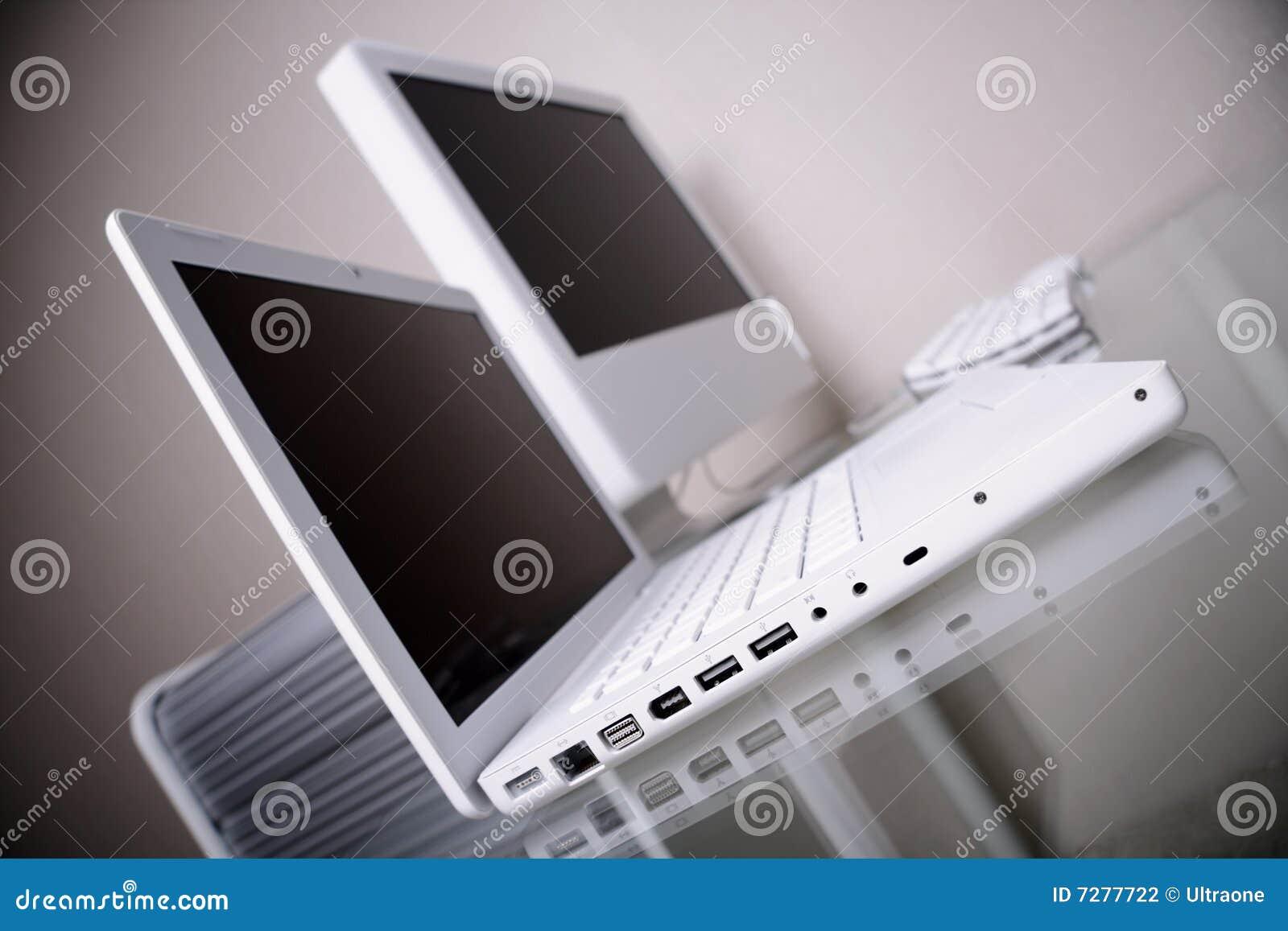 Lugar de trabajo moderno con la computadora portátil y el ordenador blancos. Hasta