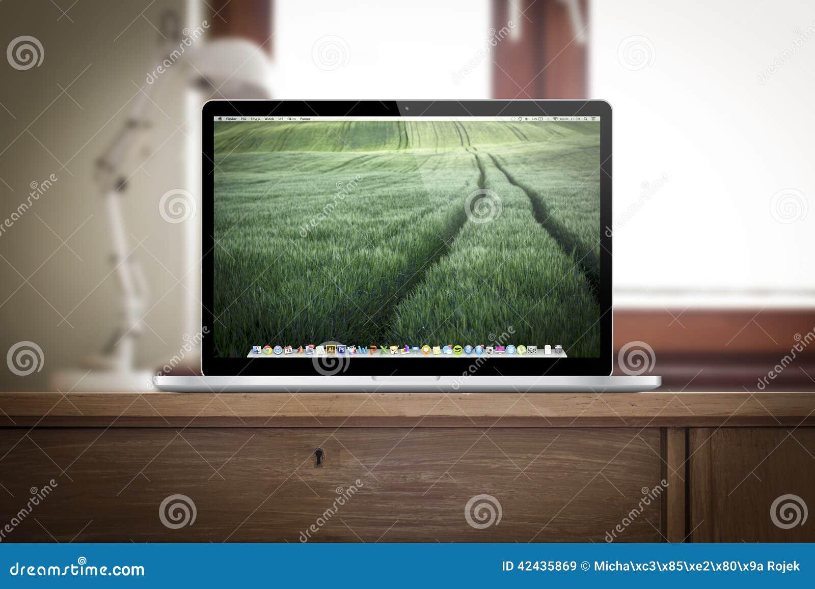 Lugar del trabajo con la favorable retina del macbook en el escritorio