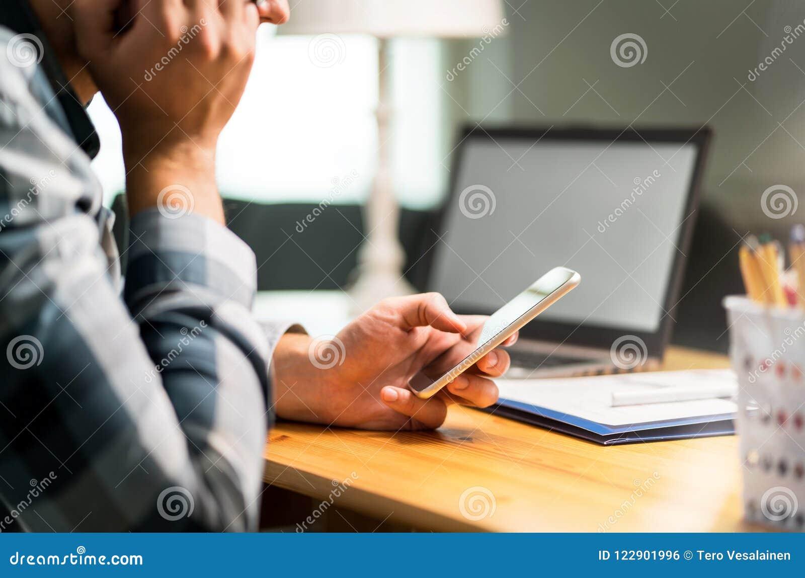 Luie arbeider die telefoon in bureau met behulp van die het werk vermijden