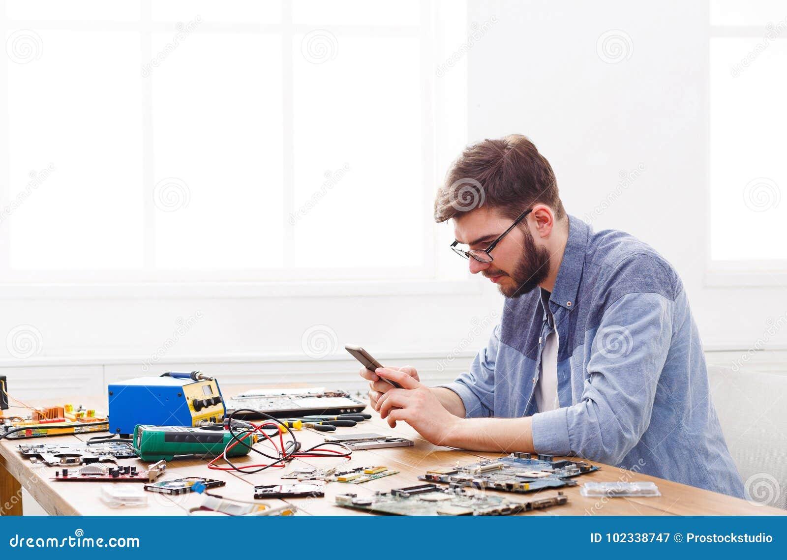 Luie hersteller het spelen smartphone in werkplaats