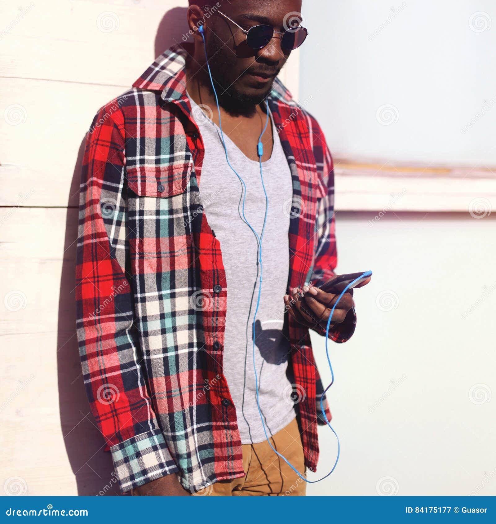 Luistert de jonge afrikaanse mens van het manierportret aan muziek op smartphone hipster - Mode stijl amerikaans ...