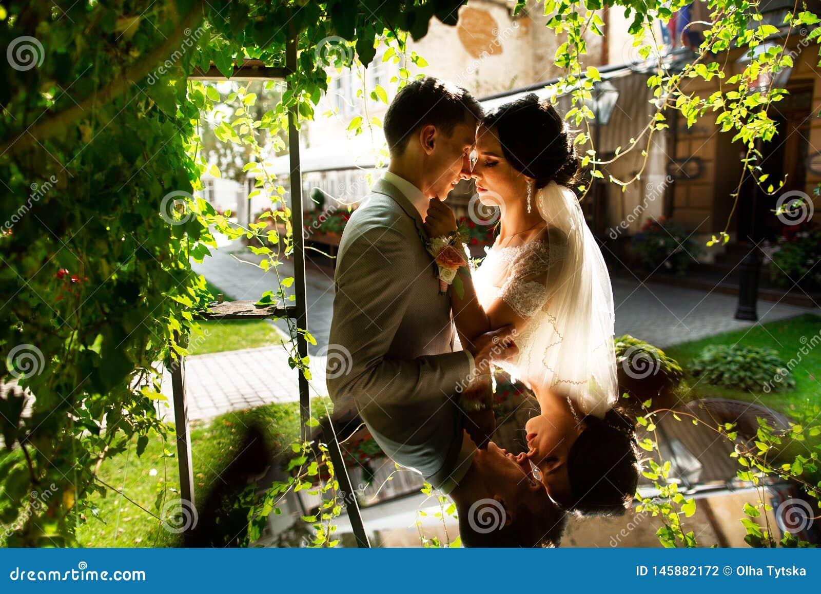 Luksus poślubiająca ślub para, państwo młodzi, pozuje w romantycznym podwórzu stary miasto