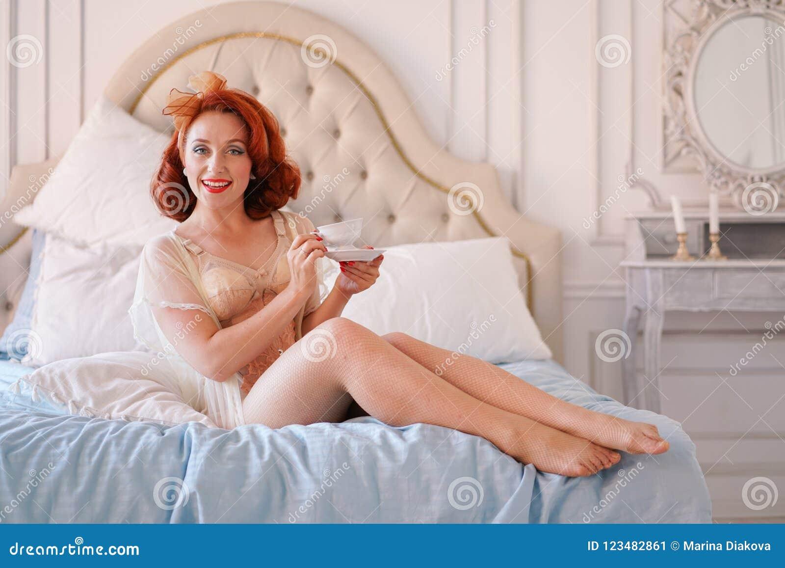 Luksusowa szpilka w górę damy ubierającej w beżowej rocznik bieliźnie pozuje w jej sypialni i filiżankę śniadaniowa herbata