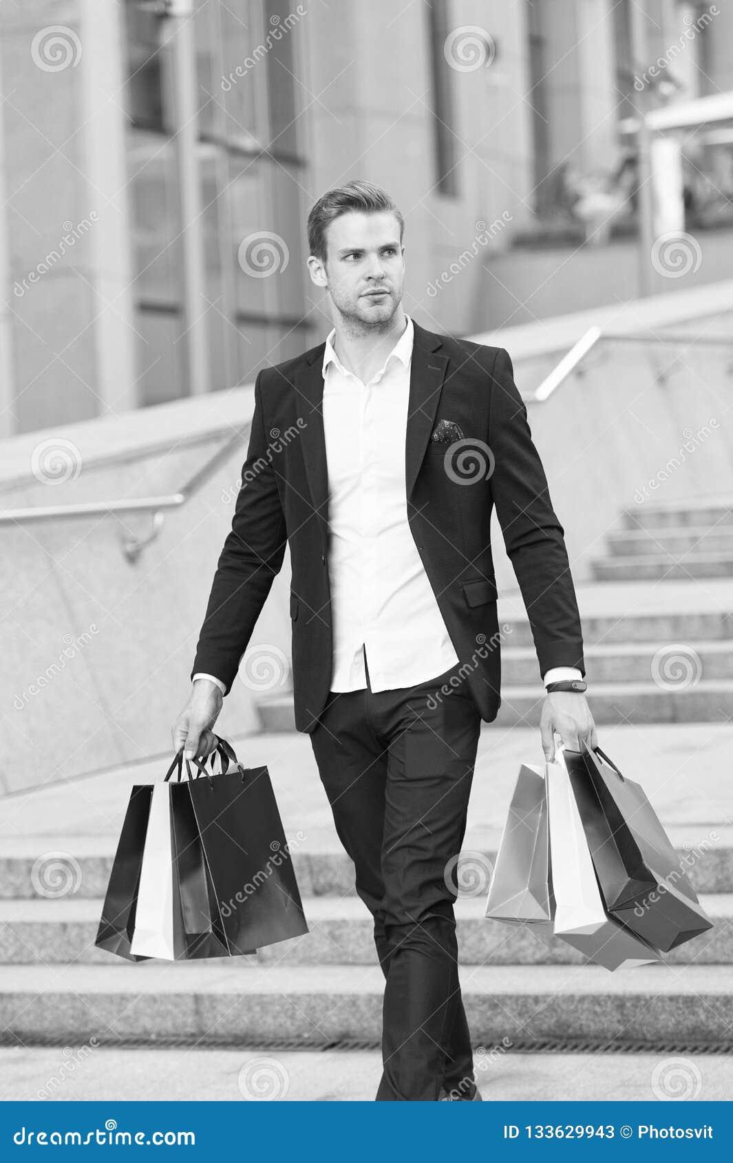 Luksusowy zakupy Butik galerii klient Mężczyzna kupujący niesie torba na zakupy miastowego tło biznesmen sukces