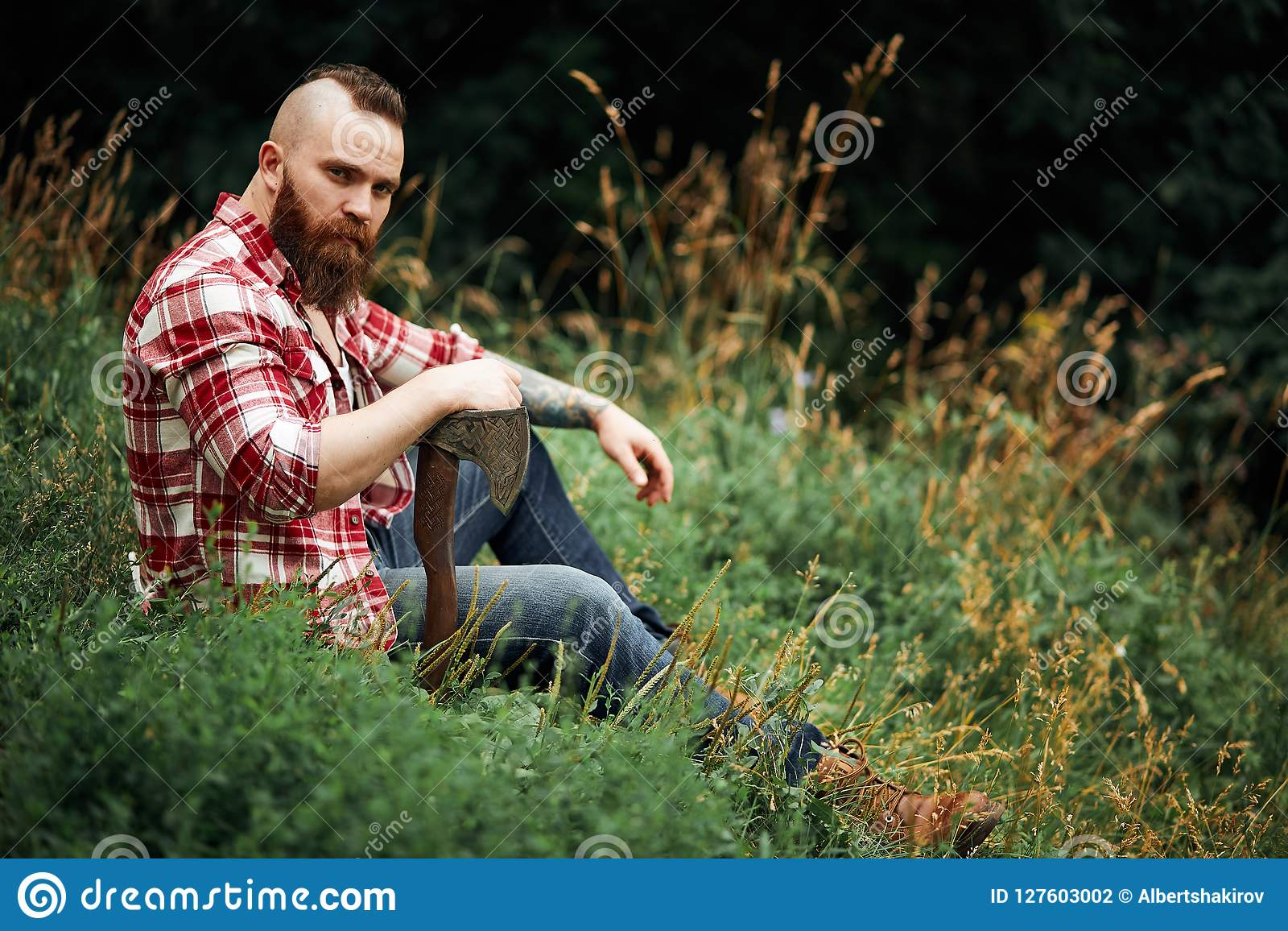 34c9afa0046 Brutal lumberjack in red shirt with beard holding axe sitting in Forest  after work