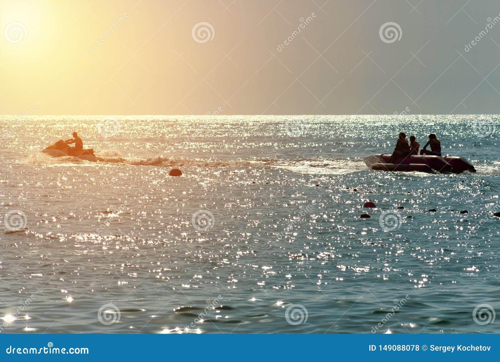 Lumi?re orange de ciel bleu sur le coucher du soleil la silhouette d un ski de jet de bateau de banane ont l amusement
