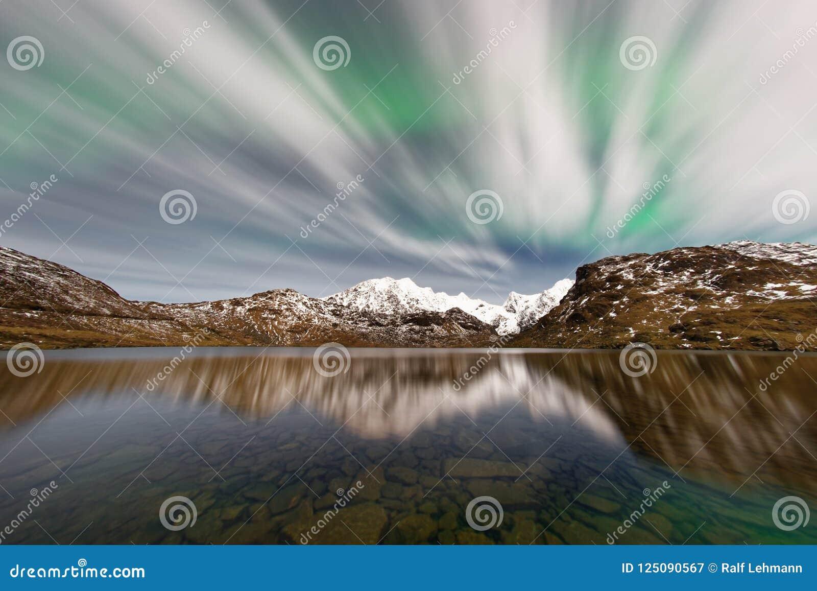 Lumières du nord derrière les nuages minces sur une gamme de montagne