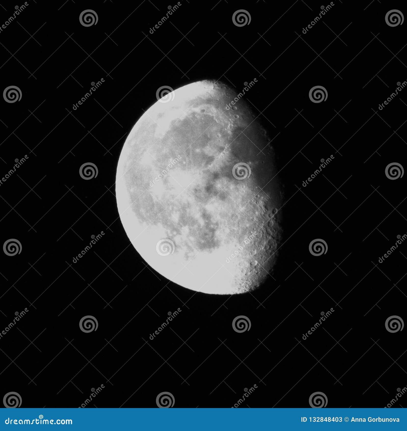 Luna de disminución en el cielo negro con los cráteres agraciados