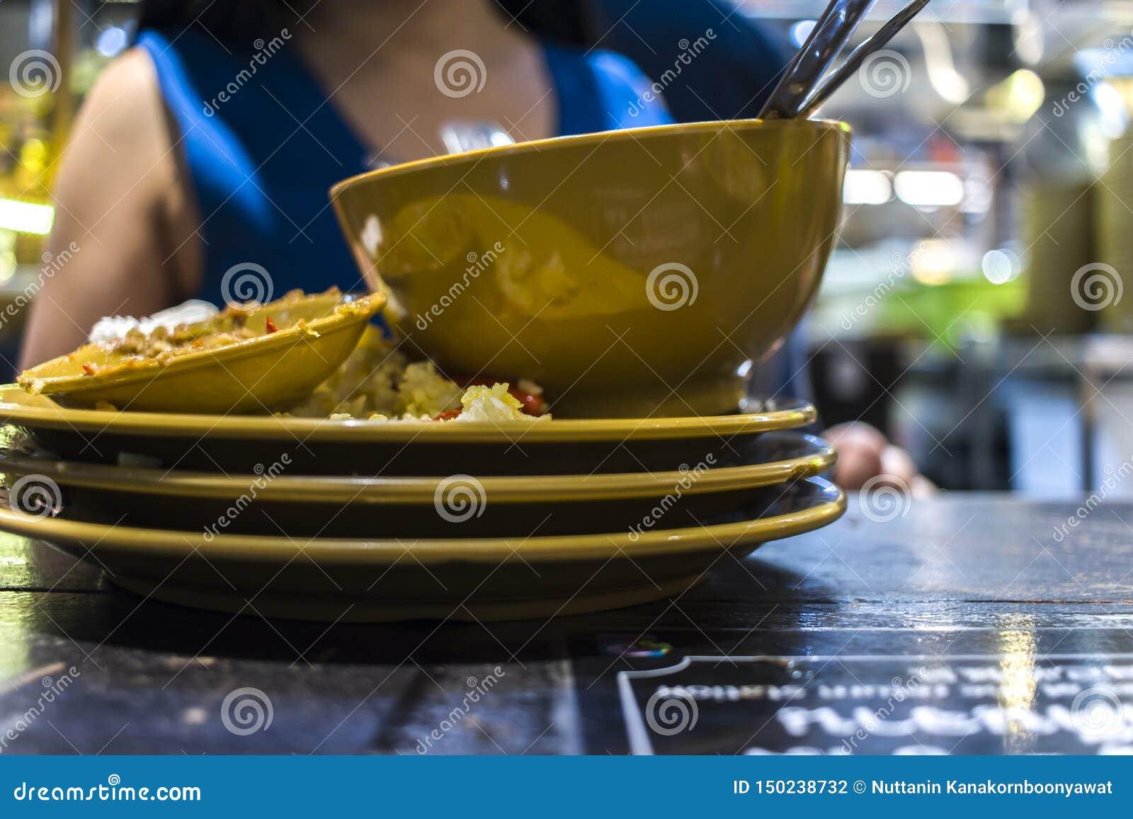 Lunch på en thailändsk restaurang En kvinna äter ris med grönsaker och soppa