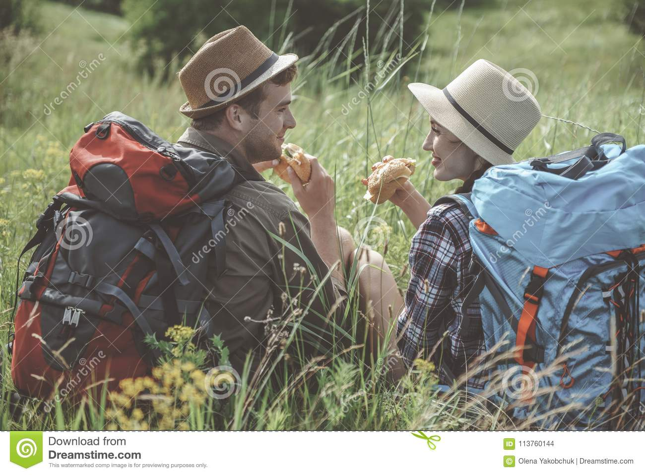 Optimistic girl and guy are eating outdoors