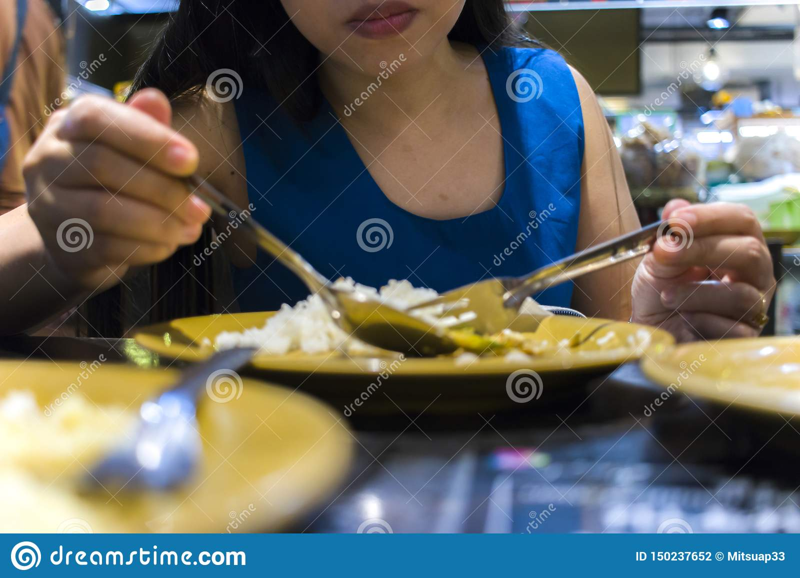 Lunch at a Thai restaurant. A woman eats rice with vegetables and soup