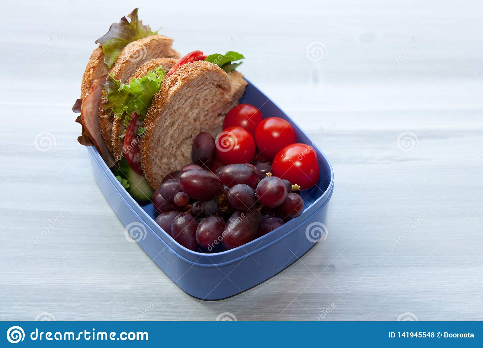 Lunchbox with sandwich, vegetables and fruits.