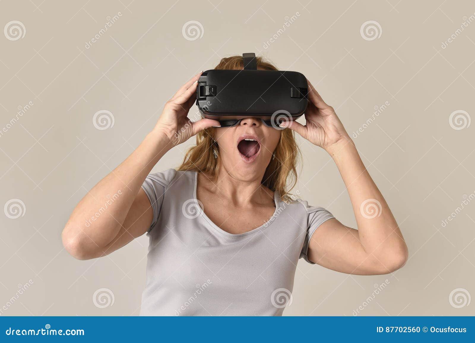 Lunettes de port de vision de réalité virtuelle du casque VR de femme blonde attirante observant la vidéo