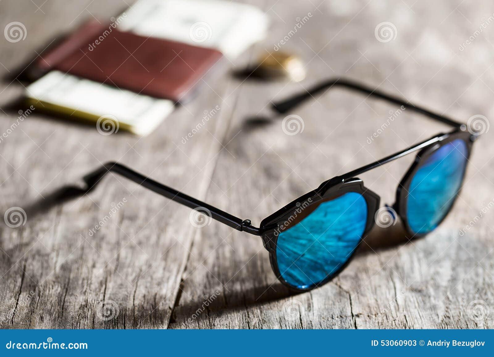 Les lunettes de soleil élégantes avec le bleu ont teinté le miroir sur le  fond en bois texturisé avec un portefeuille, des pièces de monnaie et des  dollars 9279602a13bc