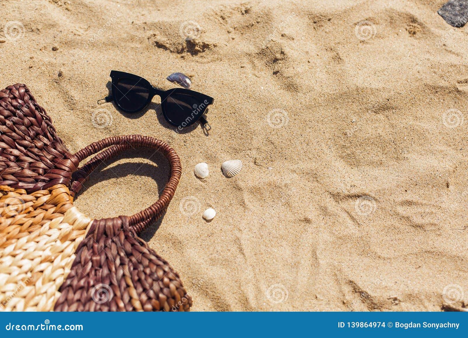 Lunettes de soleil élégantes, sac de paille sur la plage sablonneuse avec des coquillages, vue supérieure avec l espace de copie