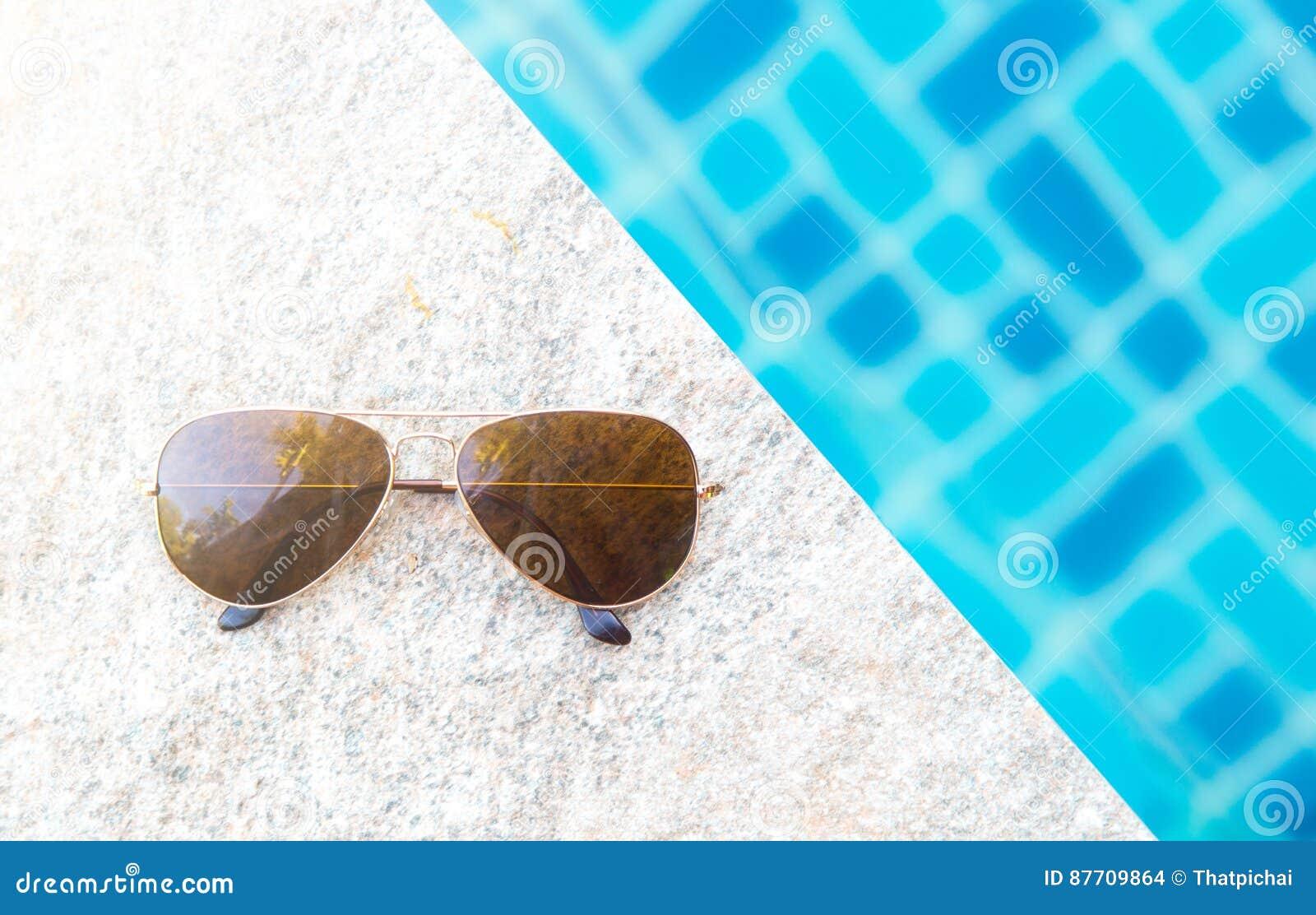 Lunettes de soleil avec la lumière naturelle sur le poolside