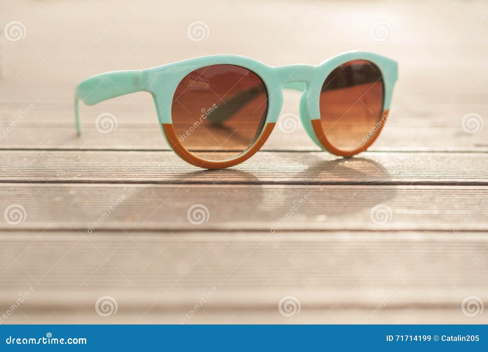 70b02221afccef Lunettes de soleil de vintage sur le bureau en bois dehors dans la vue de  plan rapproché en tant que concept UV de protection de rayons