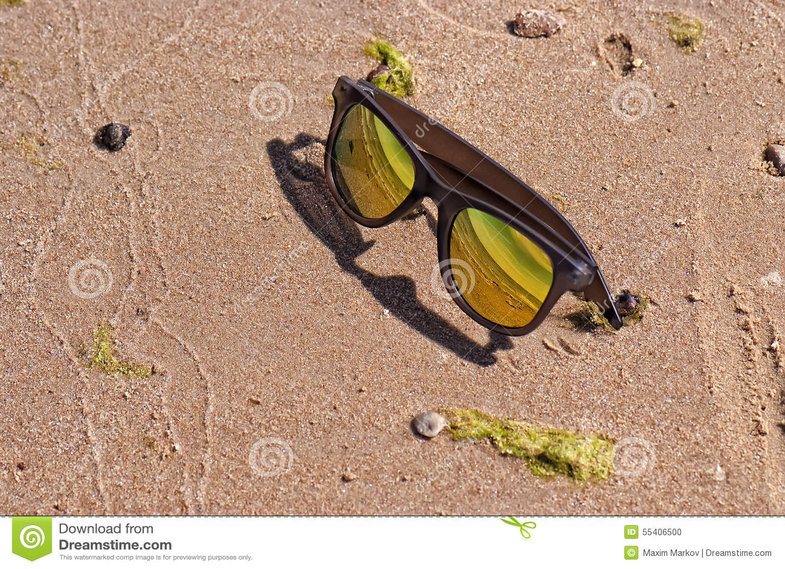 Lunettes de soleil lumineuses de couleur d or dans le sable
