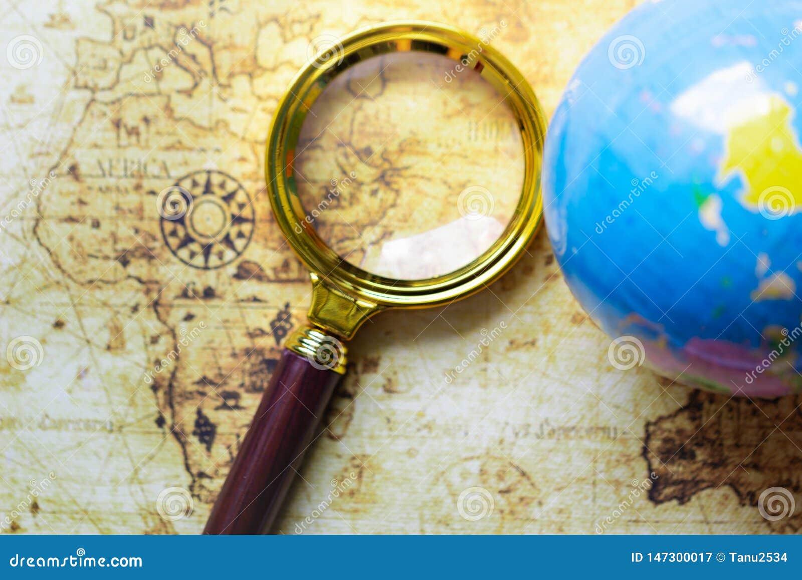 Lupa y globo en viejo fondo del mapa
