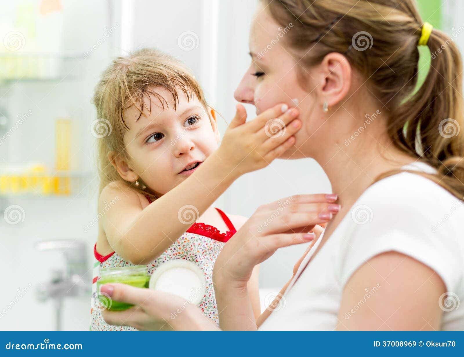 Lura att sätta kräm på hennes moders framsida i badrum royaltyfria ...