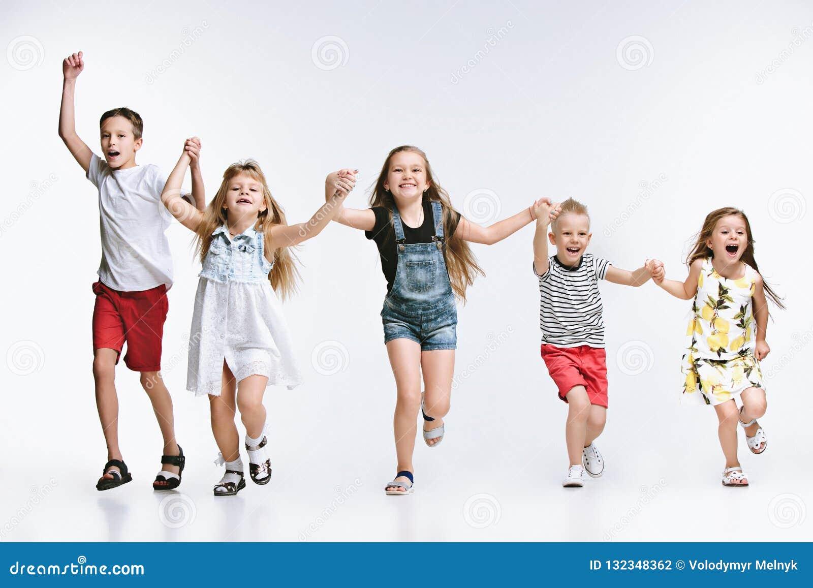 Lurar det gulliga förskolebarnet för gruppmode vänner som tillsammans poserar och ser vit bakgrund för kameran