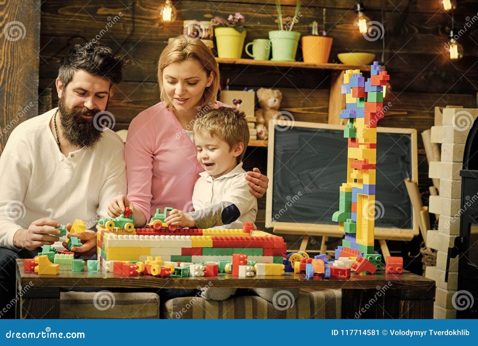 Lurar leka toys Älskvärd familj i lekrum Mamma och unge som spelar med bilar på loppspår ut ur plast- kvarter