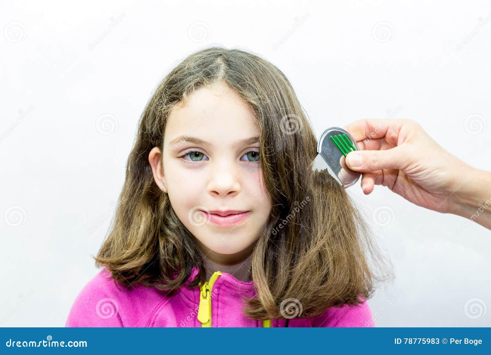 Lusbehandling Flickan får kammad för löss med lushårkammen Hon är rädd