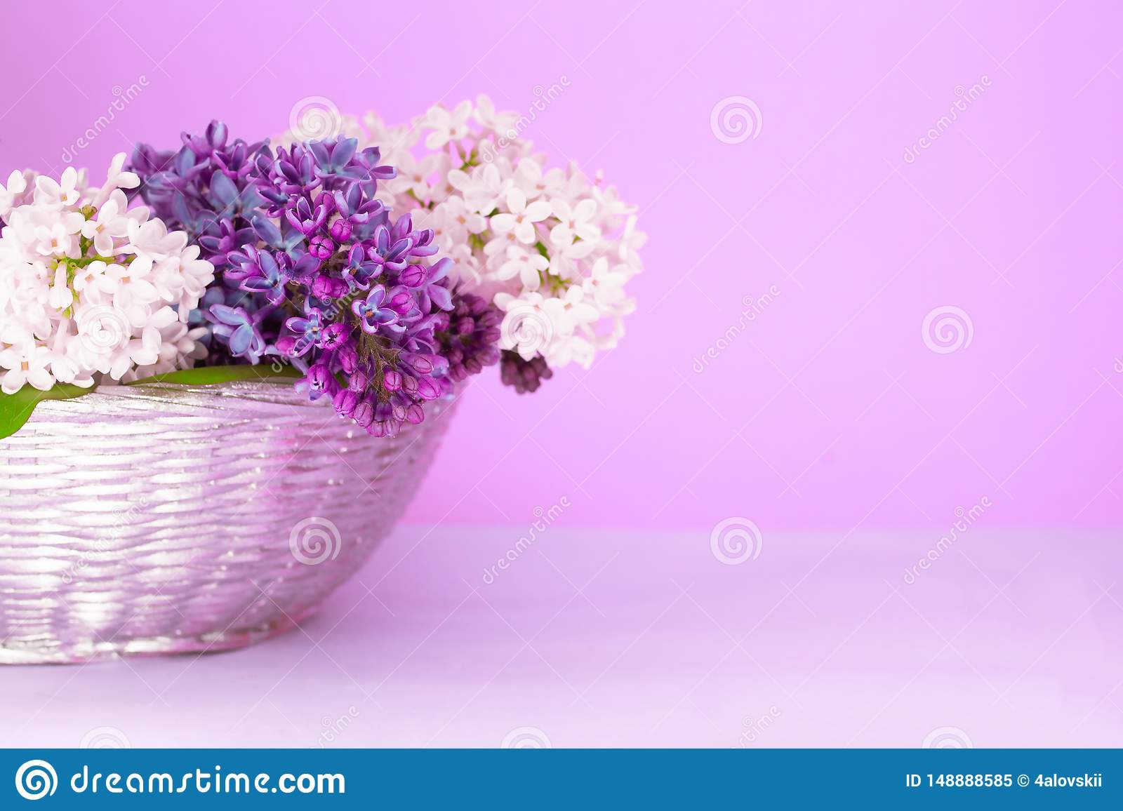 Lush multicolored bouquet of lilac flowers in a blurred purple background. Pastel greeting card concept. Copy space.