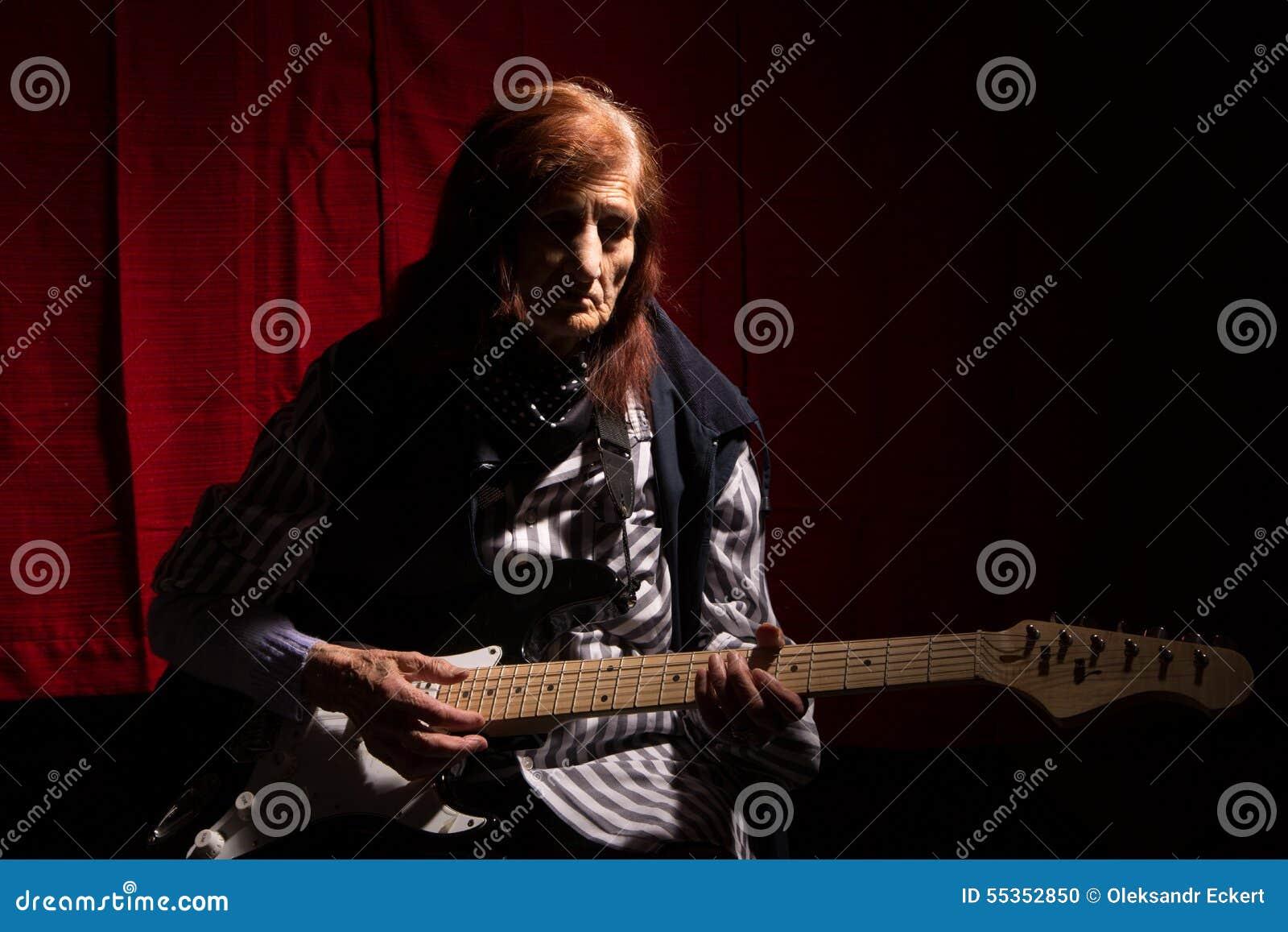 Lustige ältere Dame, die E-Gitarre spielt