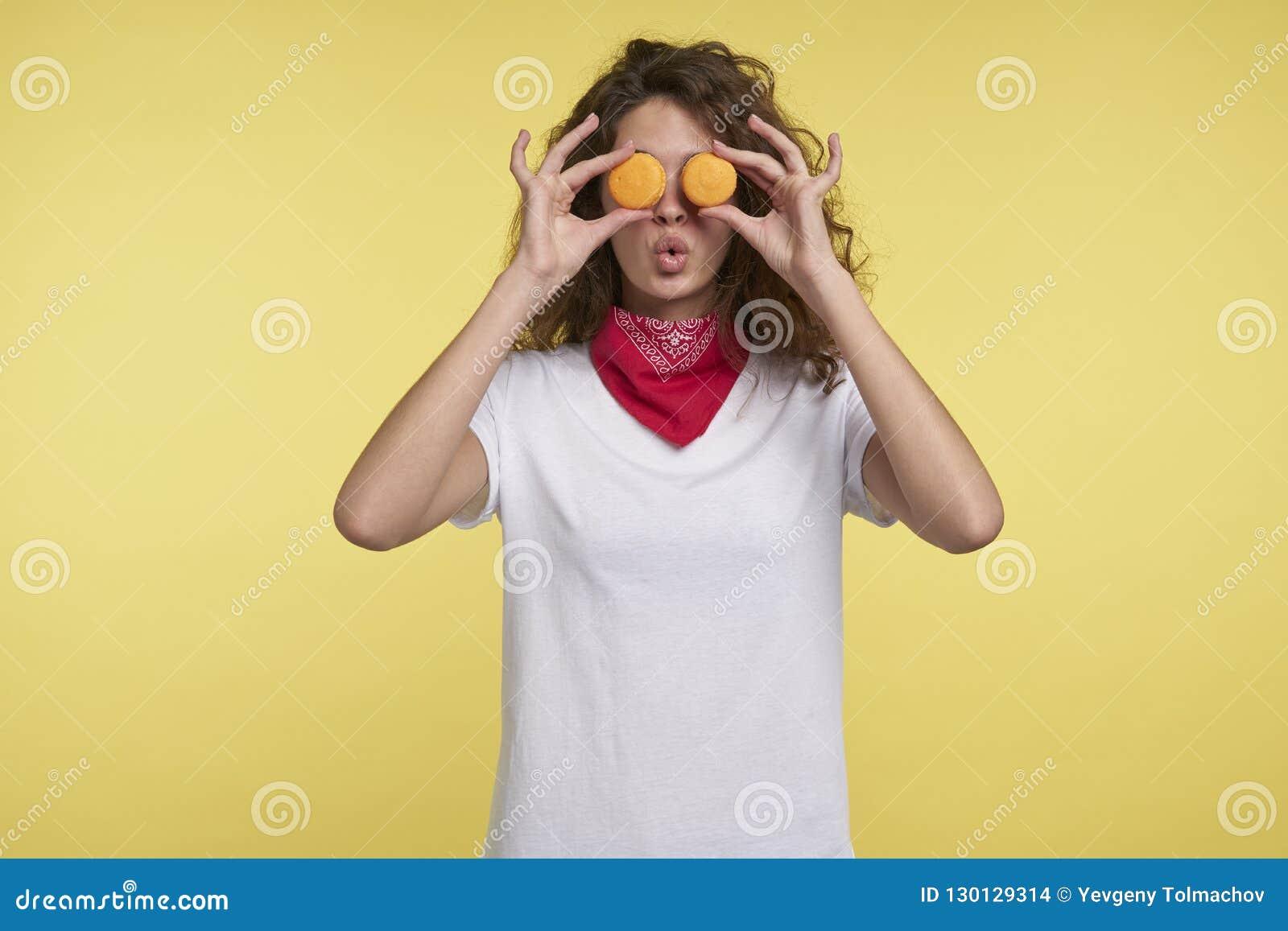Lustige junge Frau, die Makronen nahe Augen, gegen gelben Hintergrund hält