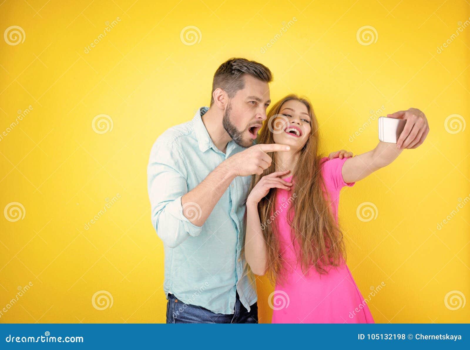 lustige junge paare die selfie auf hintergrund nehmen