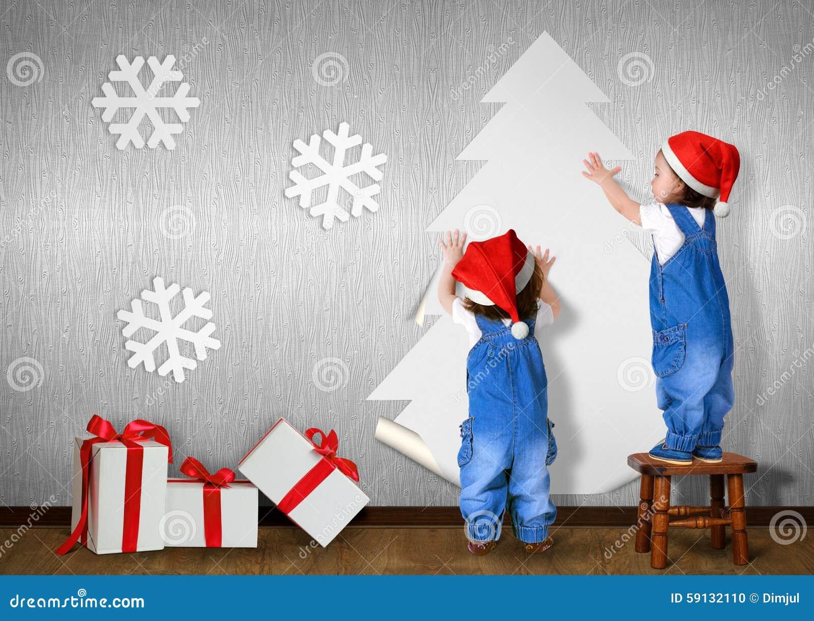 Lustige kleine Zwillinge kleideten Sankt-Hut, Kleber Weihnachtsbaum auf wal