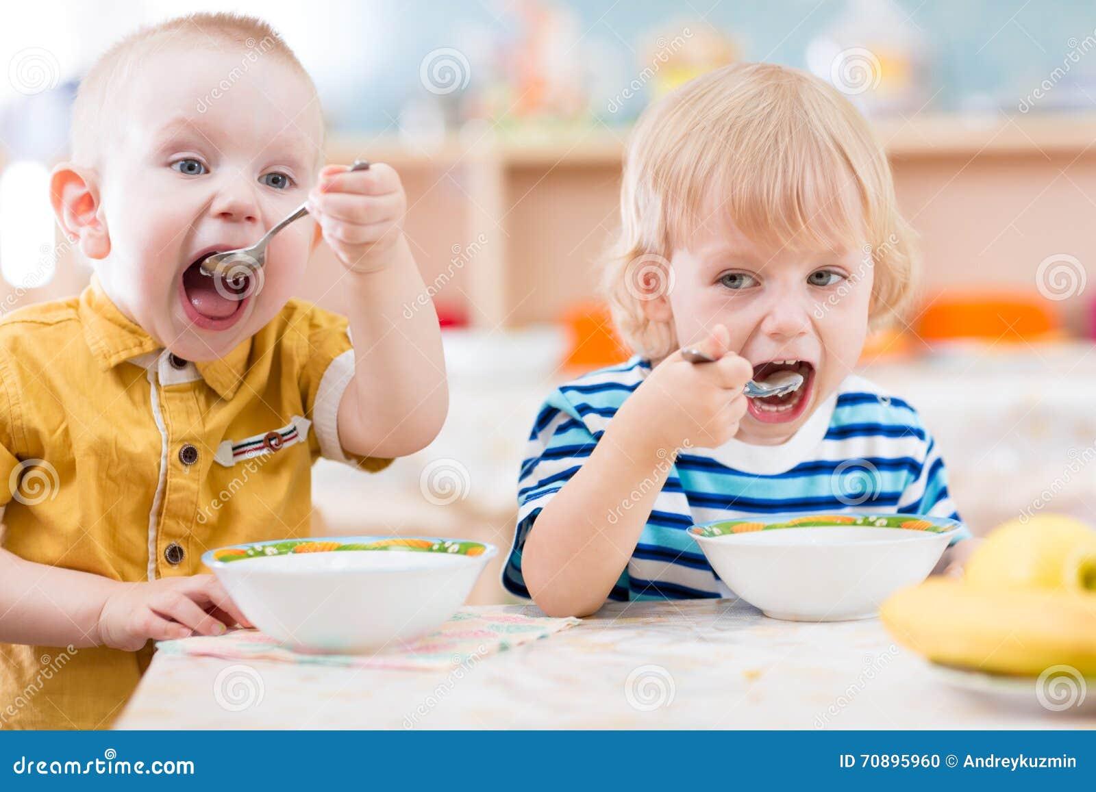 lustige kleinkinder die von den platten im kindergarten essen stockfoto bild von lustig. Black Bedroom Furniture Sets. Home Design Ideas