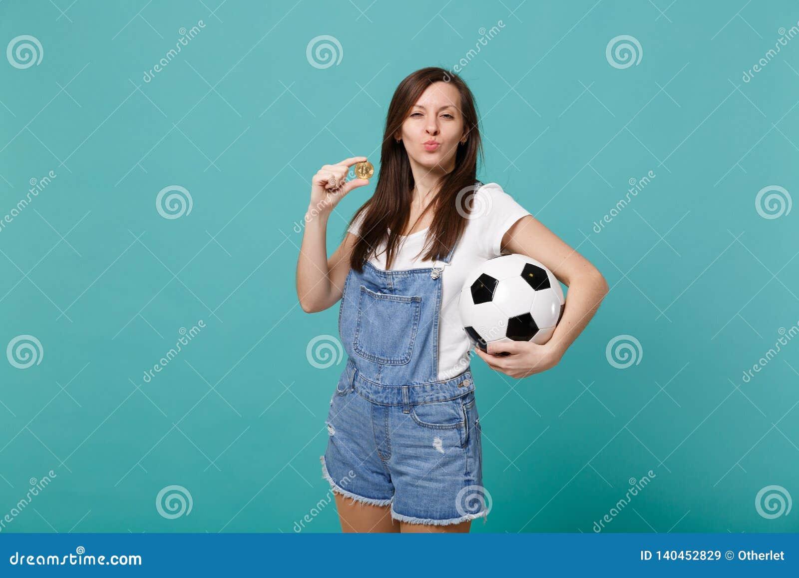Lustige Mädchenfußballfanstützlieblingsteam mit dem Fußball, bitcoin Schlagluftkuß zukünftiger Währung an lokalisiert