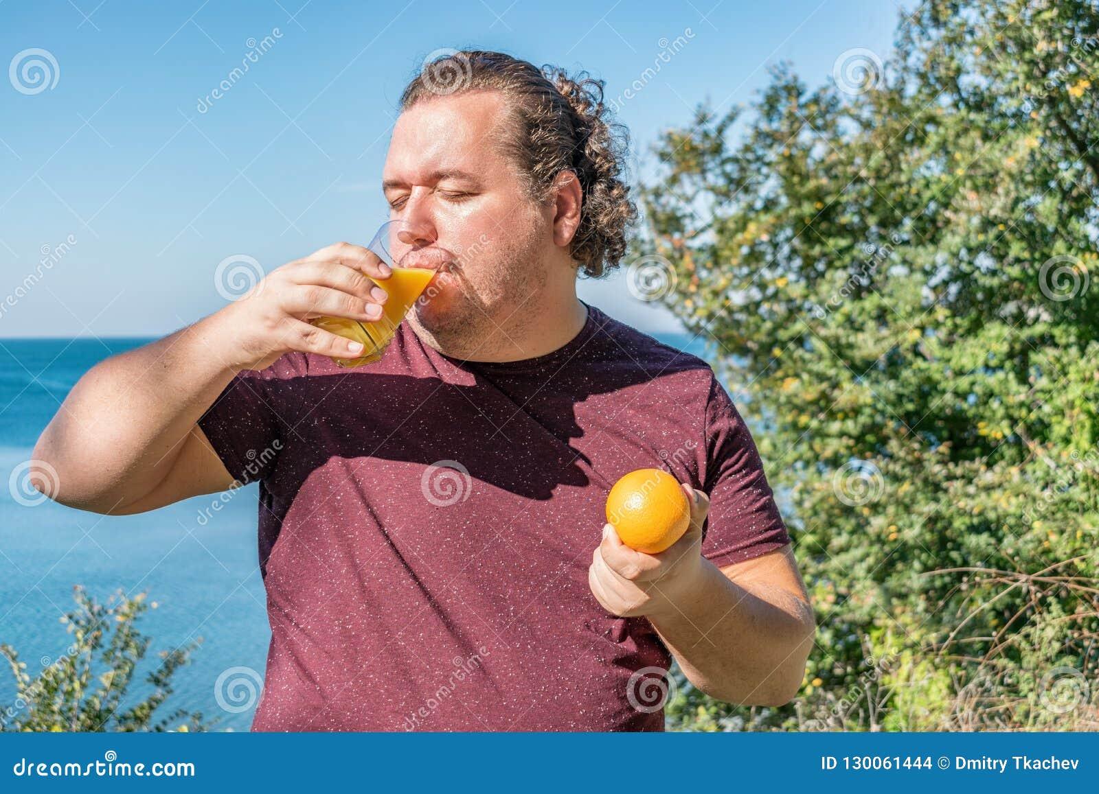 Lustiger dicker Mann auf den trinkenden Saft- und Früchten des Ozeans essen Ferien, Gewichtsverlust und gesunde Ernährung